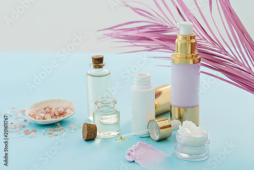 skincare beauty products concept image with pink palm leaf