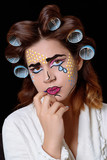 Model with pop art makeup against black background.