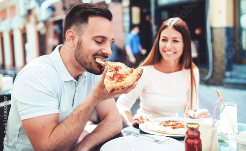 Plexiglas Pizzeria Loving couple sitting in the cafe and eating pizza. Consumerism, food, lifestyle concept