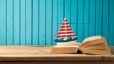 Boat and book on wooden table - 201637946
