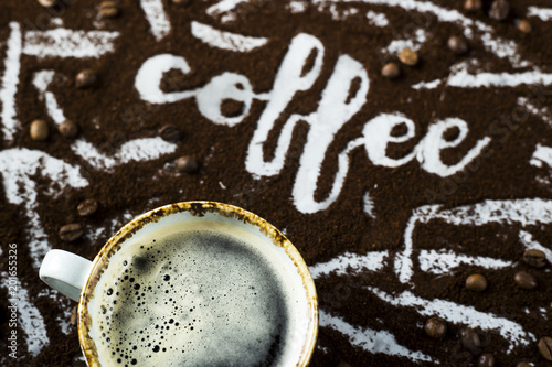 Fotobehang Koffiebonen A cup of fresh hot coffee with foam next to the word