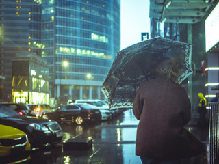 back portrait of man walking with umbrella during strong storm in urban city