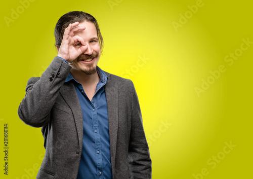 Foto Murales Handsome young man looking at camera through her fingers in ok gesture. Imitating binoculars, beautiful eyes and smile