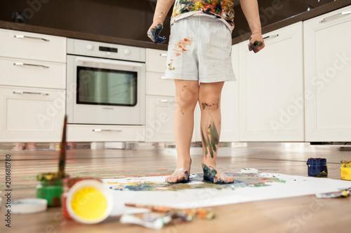 Dziecko posmarowane farbami stoi na kartce papieru. Nogi chłopca są w gwasz.