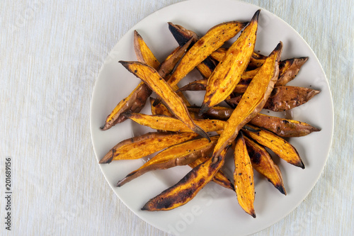 Foto Murales Oven roasted sweet potato wedges on plate , top view