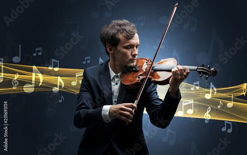 Młody muzyk mężczyzna gra na jego skrzypce z nutami w okolicy