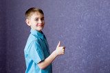 Boy in a blue shirt shows a hand gesture