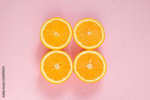Pomarańczowy pocięte na pół na różowym tle