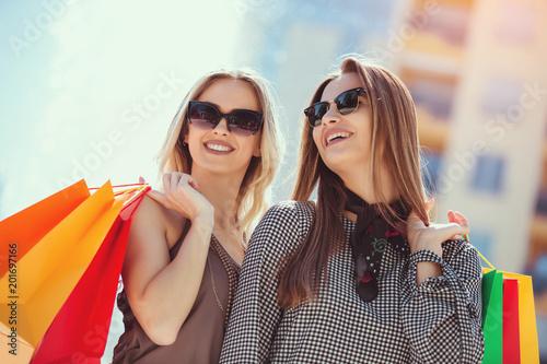 Foto Murales Happy friends shopping. Young friends enjoying shopping in the city, holding shopping bags.