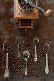 Close-up photo of metal spoons with aroma coffee beans and coffee bean grinder on black table background - 201698129
