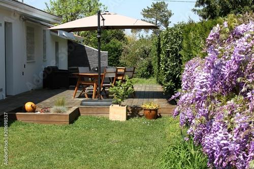 terrasse en bois exotique et salon de jardin près d'une haie de glycines en fleurs