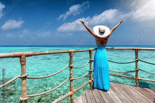 Glückliche Frau im blauen Kleid genießt die Aussicht auf das türkisfarbende Meer der Tropen