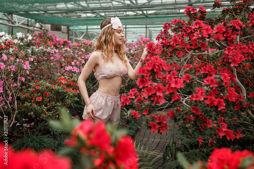 Young sexy woman posing in pajamas and sleeping mask in greenhouse full of red flowers - 201711127