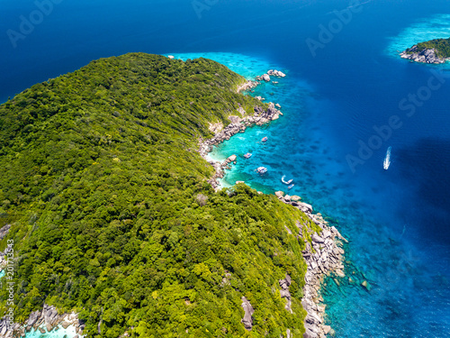 Foto Murales Aerial drone view of a boat over a coral reef next to a beautiful, empty, tree covered island