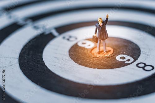miniature business standing on dartboard, financial business goals concept