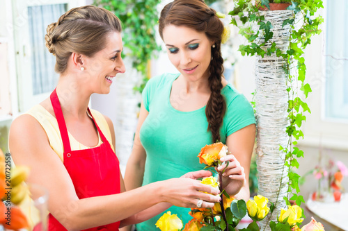 Foto Murales Florist woman selling rose bouquet to her female customer