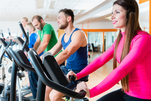 Poster Male and female athletes doing spinning on home trainers in health club gym