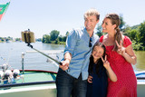 Happy family on river cruise with selfie stick in summer