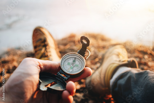 Foto Murales Hipster traveler sitting and hold in hand compass. POV view. Blurred background. Flare effect