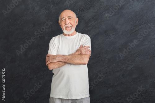 Szczęśliwy starszy mężczyzna w sportowej z skrzyżowanymi rękami