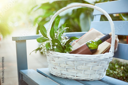 White basket with bunch of white flowers, bottle of red wine, book of love stories and plaid for picnic on blue wooden bench