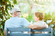 Aged man and woman relaxing on bench at tourist resort and discussing plans for journey