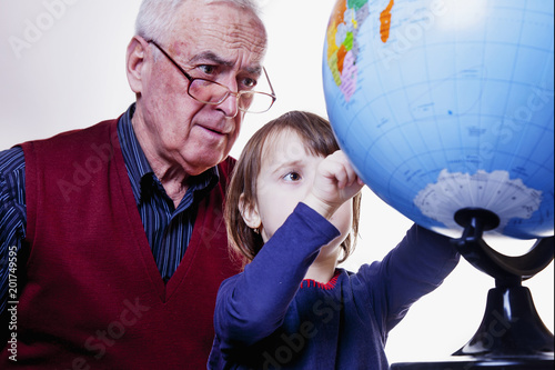 Foto Murales Global travel and geography concept. Portrait of happy grandfather and granddaughter looking at globe and planning travel.