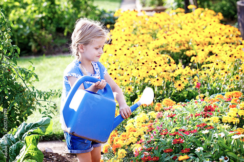 Foto Murales Child is watering flowers