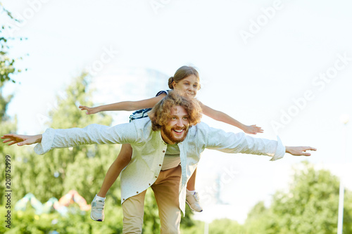 Cute little girl on her father back and the man stretching arms while having fun on summer weekend in park