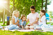 Little girls listening attentively to story or fairy-tale read by their kindergarten teacher while relaxing in park on summer day