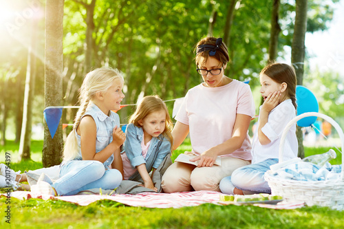 Little girls listening attentively to story or fairy-tale read by their kindergarten teacher while relaxing in park on summer day - 201754397