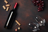 Bottle of wine, two glasses, corkscrew and corks, on rusty background top view - 201754969