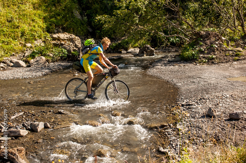 Foto Murales Mountain biker is crossing the river in the highlands of Tusheti region, Georgia