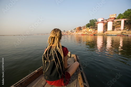 Foto Murales Woman traveler on a boat glides through the water on the Ganges river along the shore of Varanasi, India.