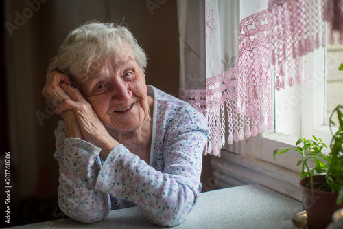 An elderly woman sitting in her home.