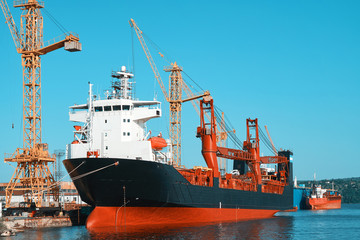 Large cargo ships. View of the sea industrial port. Unloading and loading of merchant ships. Commercial containers
