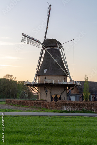 Foto Murales Landscape with traditional Dutch grain wind mill and blue sky on sunset, copy space