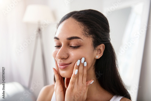 Foto Murales For healthy skin. The close up of a gorgeous dark-haired woman stretching the skin of her cheeks while doing a face-lifting massage