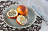 Granadilla is an exotic tropical fruit. Two fruits lie on a plate. One of the fruits is cut in half. In the frame cutlery. Close-up.