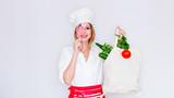 woman in cook uniform holding bag with different vegetables and american flag - 201790536