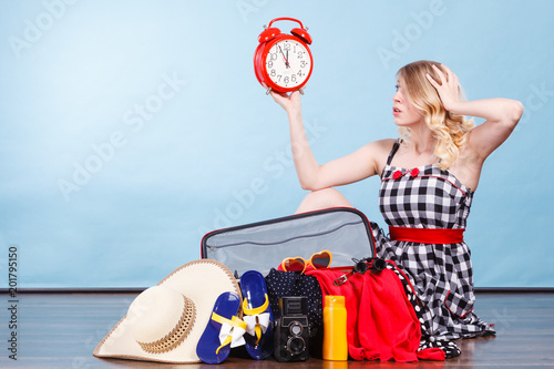 Foto Murales Woman sitting with suitcase holding old clock