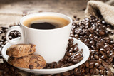 cup of coffee with two cookies on wooden background with heap of coffee beans