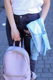 Teenager standing with light pink backpack outdoors. Concept of fashion youth and strolling. - 201818160
