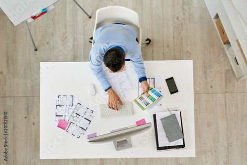 Directly above view of creative interior designer sitting at desk and working on ambitious project, interior of modern office on background