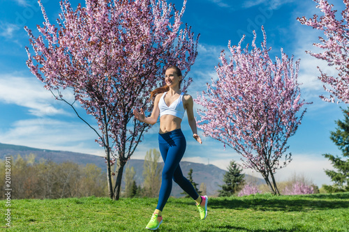 Fototapeta Fit woman running for fitness on a spring day
