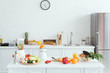 interior of white light kitchen with delicious fruits and vegetables on kitchen counter