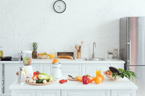 Foto Murales interior of white light kitchen with delicious fruits and vegetables on kitchen counter