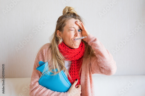 Foto Murales Funny picture of sick woman measuring temperature with thermometer in her mouth