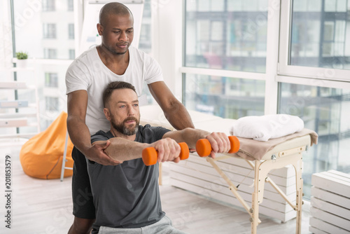 Foto Murales Professional training. Serious bearded man working out with the coach while doing rehabilitation therapy
