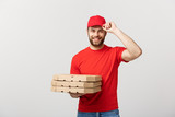 Delivery Concept: Young caucasian Handsome Pizza delivery man holding pizza boxes isolated over grey background